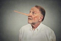 Man med den långa näsan som ser upp Lögnarebegrepp fotografering för bildbyråer