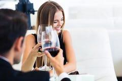 Man med den lyckliga eleganta kvinnan som dricker rött vin Royaltyfri Foto