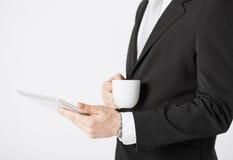 Man med den minnestavlaPC och koppen kaffe Arkivbild