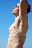 Man med den perfekta kroppen med stängda ögon som är främsta av himmel Arkivbild