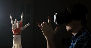 Man med den robotic handen för styrning Innovativ robotic hand - som göras på skrivaren 3D futuristic teknologi Modig bransch och arkivfilmer
