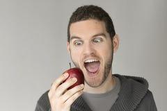 Man med den roliga framsidan som ser ett äpple Royaltyfria Bilder