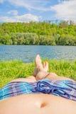 Man med den rutiga badningsnedsteget och kal fot på sjön/floden, äng/gräs Arkivfoton