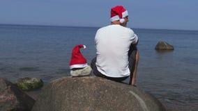 Man med den Santa Claus hatten på stenen nära havet arkivfilmer
