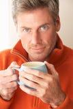 Man med den varma drinken arkivfoto