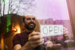 Man med det öppna banret på stång- eller restaurangfönstret Arkivfoto