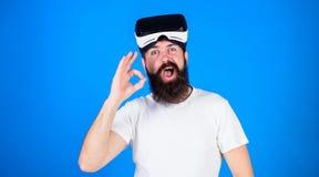 Man med det långa skägget och roliga framsidan som visar reko gest Hipsteren med det moderiktiga skägget som bär VR, rullar med ö Royaltyfri Fotografi