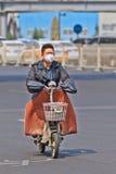 Man med det 3M munlocket på e-cykeln, Peking, Kina Arkivbild