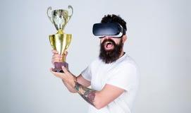 Man med det stilfulla skägget i VR-exponeringsglas som poserar med det 1st priset som isoleras på grå bakgrund Guld- lycklig skäg Arkivfoton