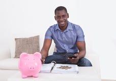 Man med dokumentet och Piggybank Royaltyfria Foton