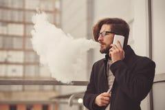 Man med e-cigaretten och mobiltelefonen Royaltyfri Bild