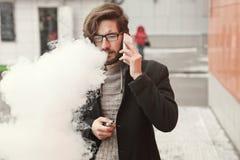 Man med e-cigaretten och mobiltelefonen Royaltyfria Bilder