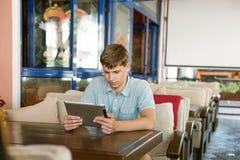 Man med en bärbar dator i ett kafé Arkivbild