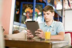 Man med en bärbar dator i ett kafé Royaltyfria Bilder