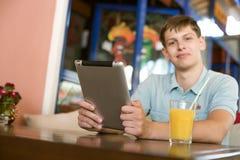 Man med en bärbar dator i ett kafé Royaltyfri Bild