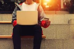 Man med en bärbar dator och en kreditkort Royaltyfri Bild
