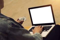 Man med en bärbar dator och en kreditkort Royaltyfria Bilder