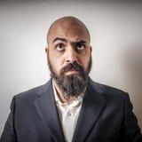 Man med en dräkt och ett skägg och konstiga uttryck arkivfoto