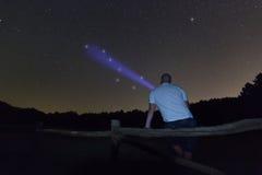 Man med en ficklampa som pekar till den stora skopan Polstjärnanstjärna för stjärnklar natt, Ursa Major, Karlavagnenkonstellation Arkivbilder