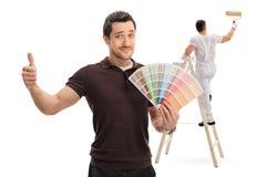 Man med en färgprovkarta och målare på stege Arkivbilder