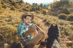 Man med en hatt i ett fält med en cigarett och en hund royaltyfria foton