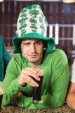 Man med en hatt som rostar ett öl Arkivbild