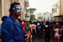man med en maskering som håller ögonen på karnevalhändelsen på gatorna av staden royaltyfri bild