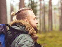 Man med en ryggsäck och ett skägg som fotvandrar i skogen royaltyfria bilder
