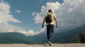 Man med en ryggsäck som upptill tycker om landskapet av berget Turist- handelsresande på bakgrunden av stock video