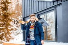 Man med en snöskyffel nära huset fotografering för bildbyråer
