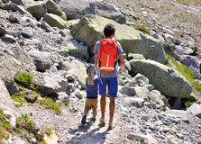 Man med en son i berg Royaltyfria Bilder