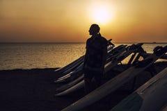 Man med en surfingbräda som får en kontur mot gryningen och set Arkivbild