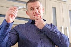 Man med en termometer i hans hand Ökande kroppstemperatur arkivbilder