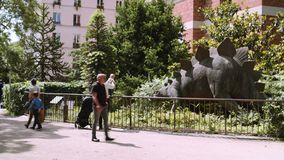Man med ett barn som ser ett diagram av en dinosaurie i botanisk trädgård i Paris lager videofilmer