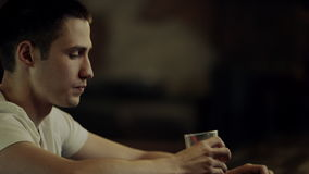 Man med ett exponeringsglas av drinken arkivfilmer