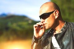 Man med exponeringsglas och det svarta omslaget som röker cigaretten Royaltyfri Bild