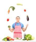 Man med förklädet som jonglerar med grönsaker, medan förbereda mat Royaltyfria Foton