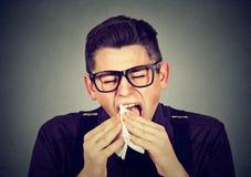 Man med förkylning som nyser i silkespapper Arkivbilder