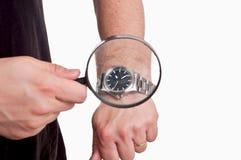 Man med förstoringsapparaten i handen som ser hans klocka på den vita backgroen Royaltyfri Foto
