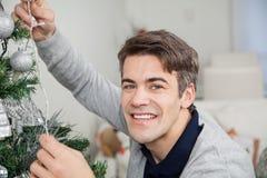 Man med felika ljus som dekorerar julgranen Royaltyfri Foto