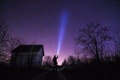Man med ficklampan nära huset och stjärnor på mörk himmel Royaltyfri Bild