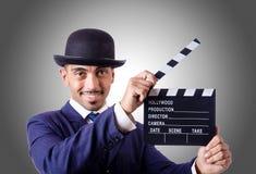 Man med filmclapperen mot lutningen Royaltyfri Bild