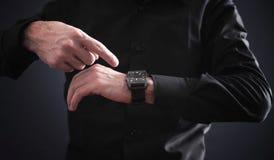 Man med fingret som pekar hans armbandsur royaltyfri bild