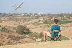 Man med fjärrkontrollnivåflyg i luft arkivfoto
