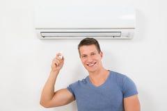 Man med fjärrkontroll som fungerar luftkonditioneringsapparaten Royaltyfri Bild