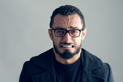 Man med frustrerat uttryck på grå färger arkivbilder