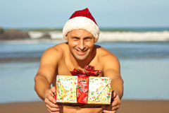 Man med gåva på stranden Royaltyfri Bild