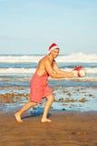 Man med gåvan på stranden Royaltyfri Bild