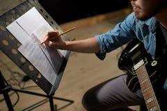 Man med gitarren som skriver till musikboken på studion arkivfoto