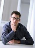Man med glasögon i regeringsställning arkivfoto